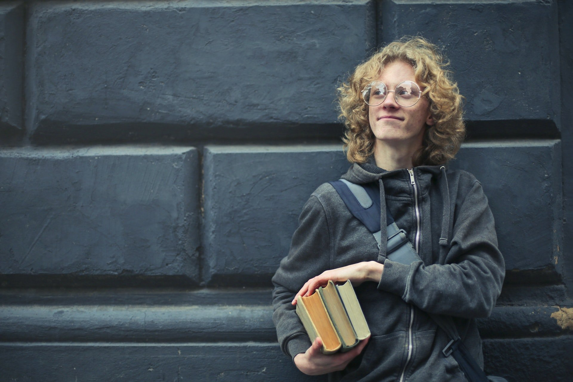High school boy holding books and looking content in that moment.