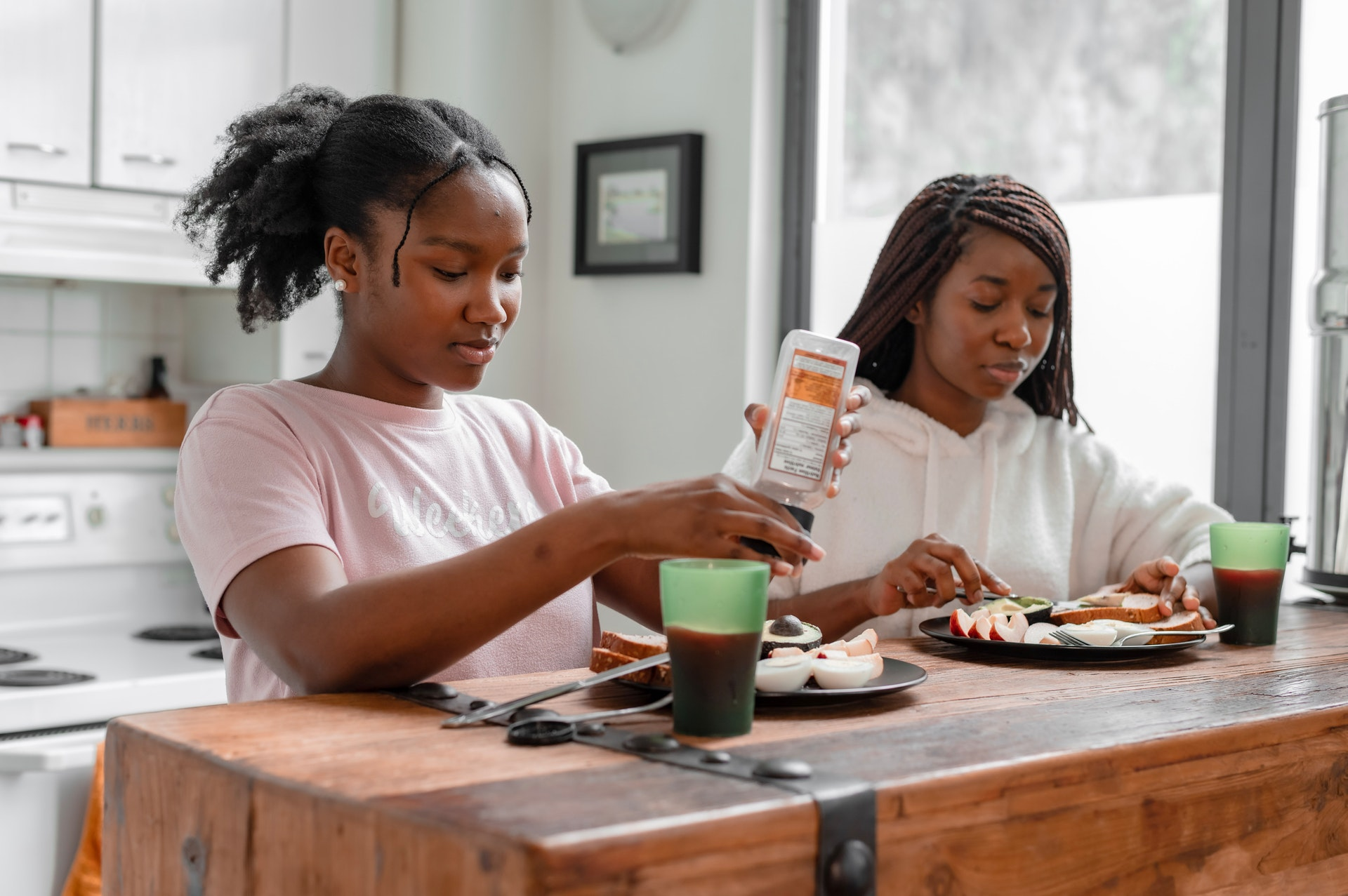 Two teenage women making themselves a nutritious lunch at home.
